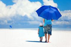 Father and daughter walking at beach. Father and daughter at beach with umbrella to hide from sun Stock Image