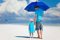 Father and daughter walking at beach Stock Photo