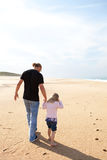 Father and daughter walking at the beach Stock Photos