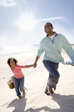 Father and daughter walking on beach Stock Photography