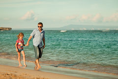 Father and daughter walking on the beach Stock Photography
