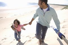 Father and daughter walking on beach, elevated view Stock Photo