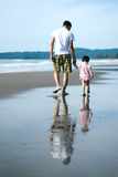 Father and daughter walking on the beach Stock Photos