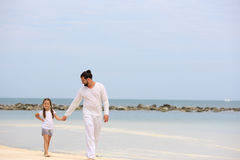 Father and daughter walking on deserted tropical beach together happy loving vacation Stock Images