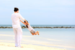 Father and daughter walking on deserted tropical beach together happy  loving vacation Stock Photos
