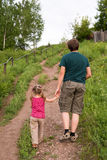 Father and daughter walking on a hill Royalty Free Stock Images