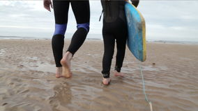 Father and Daughter Walking to the Sea to go Body Boarding stock footage