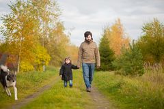 Father and daughter walking together with dog, autumn day. stock images