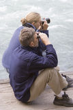 Father and daughter watching salmon run Stock Photo