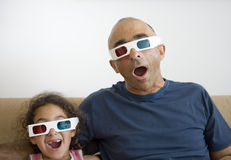 Father and daughter watching television in 3D royalty free stock image