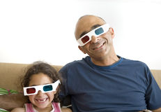 Father and daughter watching television in 3D Stock Photography