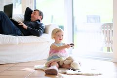 Father and daughter watching tv at home. Cute little child, 3 years old preschooler girl watching tv lying together with her father comfortable on the tiles Stock Image