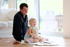 Father and daughter watching tv at home. Cute little child, 3 years old preschooler girl watching tv lying together with her father comfortable on the tiles Stock Images