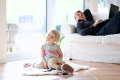 Father and daughter watching tv at home. Cute little child, 3 years old preschooler girl watching tv lying together with her father comfortable on the tiles Royalty Free Stock Photography