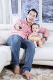 Father and daughter watching TV with popcorn. Young father and daughter sitting on the couch while watching TV and eating popcorn with winter background on the Stock Image
