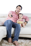 Father and daughter watching tv on studio. Image of Asian father and daughter watching tv together while eating popcorn in the studio Stock Photography
