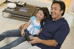 Father and Daughter Watching TV Together in living room high angle view Stock Photo