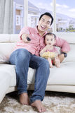 Father and daughter watching TV together. Young Asian father and daughter watching TV together while eating popcorn and sitting on the couch Stock Photography