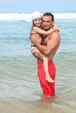 Father and daughter in water. Father and daughter at the beach stock photography