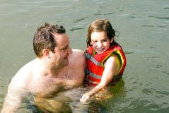 Father and Daughter in Water. A man holding his daughter while playing in the water stock photo
