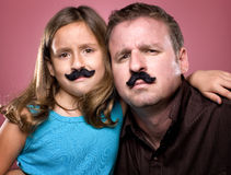 Father and Daughter Wearing Fake Mustaches. A father and daughter pose with fake mustaches royalty free stock image
