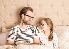 Father and daughter wearing pyjamas in a bed. Happy smiling caucasian father and daughter looking at each other while wearing pyjamas and glasses in a bed Royalty Free Stock Images
