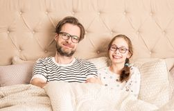 Father and daughter wearing pyjamas in a bed. Portrait of happy smiling caucasian father and daughter wearing pyjamas and glasses in a bed. Morning in a bedroom Stock Photos