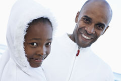 Father and daughter (8-10) in white clothing standing on beach, smiling, close-up, portrait royalty free stock images
