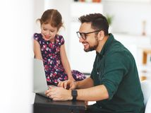 Father and  daughter working at a computer at home Stock Photography