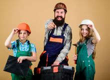 Father and daughter in workshop. Family teamwork. Repair. Repairman in uniform. Engineer. Bearded man with little girls stock photography