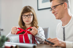 Father and daughter wrapping Christmas present at home stock image