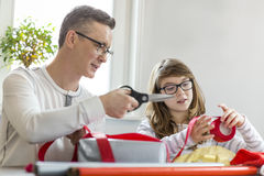 Father and daughter wrapping Christmas presents at home Royalty Free Stock Image