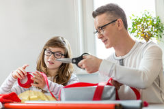 Father and daughter wrapping Christmas presents at home royalty free stock photography