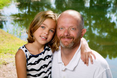 Father With Daughter. A young girl sits on her dad's lap for a portrait by a pond Stock Photo