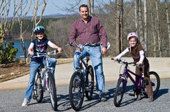 Father and Daughters Bike Riders. A man and his two daughters ready to ride their new bicycles Stock Photos