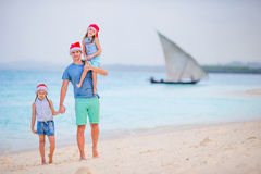 Father and daughters on Christmas vacation. Christmas family holidays on the beach Stock Photos