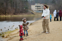 Father and daughters feeding ducks at autumn Stock Image