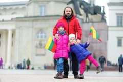 Father and daughters with a flag on Lithuanian independence day holding tricolor Lithuanian flag Royalty Free Stock Photos