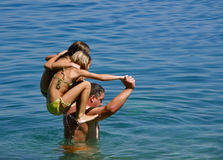 Father with daughters in fun on sea. Father holding daughters on shoulders in the water Stock Images
