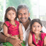 Father and daughters. Happy Indian family at home. Asian father and daughters sitting on sofa smiling. Parent and children indoor lifestyle Stock Photos