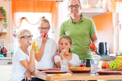 Father and daughters in kitchen eating healthy Royalty Free Stock Images