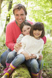 Father and daughters outdoors in woods sitting Stock Photos