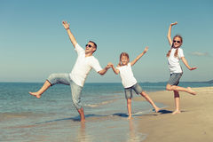 Father and daughters playing on the beach at the day time. Royalty Free Stock Images