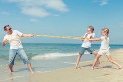 Father and daughters playing on the beach at the  day time. Royalty Free Stock Photography