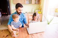Father and daughters, playing on laptop, sitting in kitchen Royalty Free Stock Photos