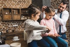 father and daughters preparing for school and work in morning on kitchen royalty free stock photos
