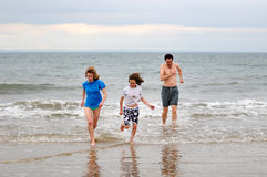Father and daughters running in the sea Stock Photos