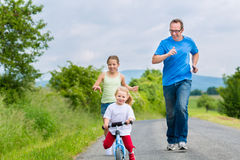 Father and daughters running on street Royalty Free Stock Photo