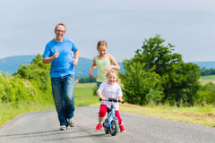Father and daughters running on street Stock Image