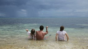 Father with daughters throw pebbles into the sea. stock video footage